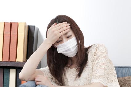 風邪を引いて熱や痛みに困っている女性