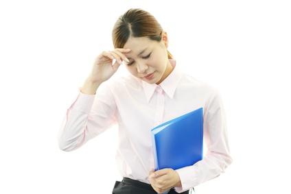 頭痛に悩まされる仕事中の女性のイメージ