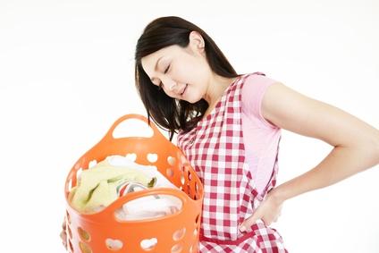 腰痛に悩んでいる主婦のイメージ写真