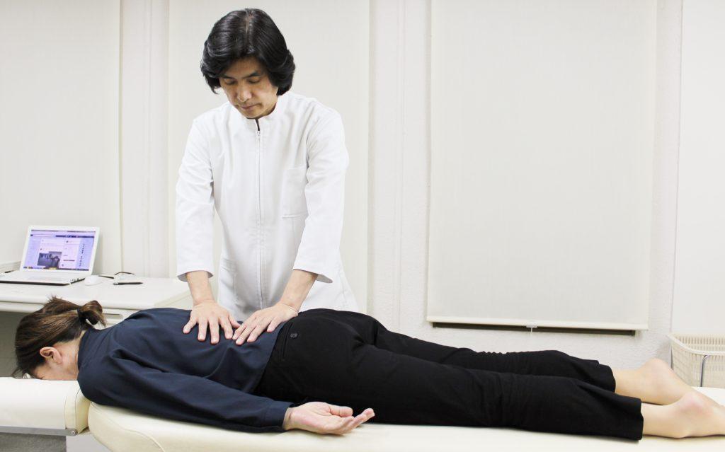 腰痛、ぎっくり腰の改善のため上原宏がDRT(ダブルハンドリコイルテクニック)の施術をしている写真