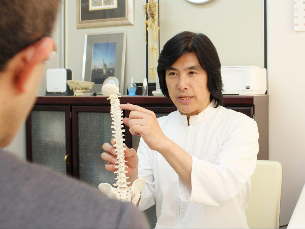 頭痛の原因は背骨のズレにあることを説明している院長の上原宏