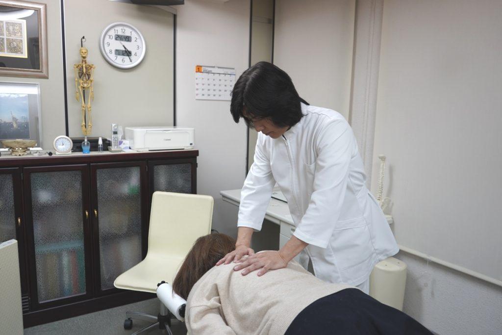上原宏がDRT施術で背骨を調整している写真